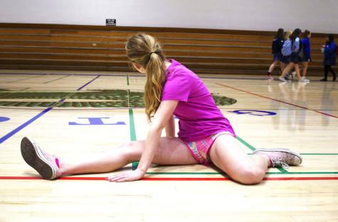 Kara Barberich stretches before track hurdles.