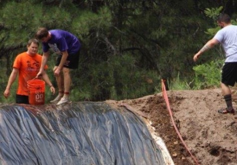 These participants prepare for the final obstacle in their mud race.