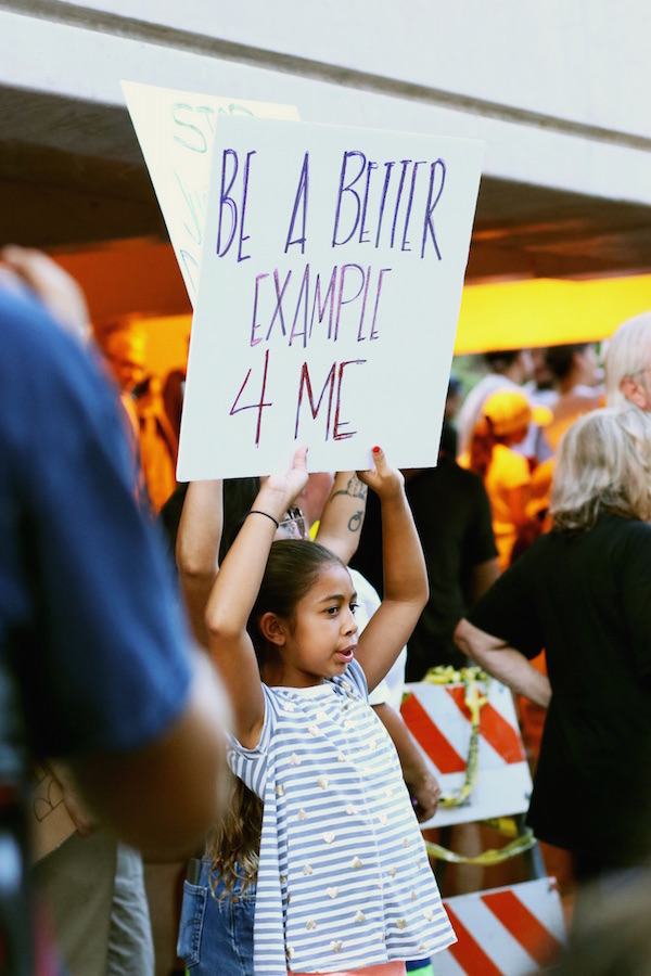 A small child among a crowd of protesters holds up a sign that reads,