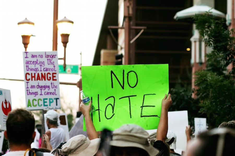 A protester holds up a neon-green sign that says