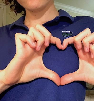 A Xavier student makes a heart symbol over her Xavier uniform, showing how Xavier students care for the world around them.