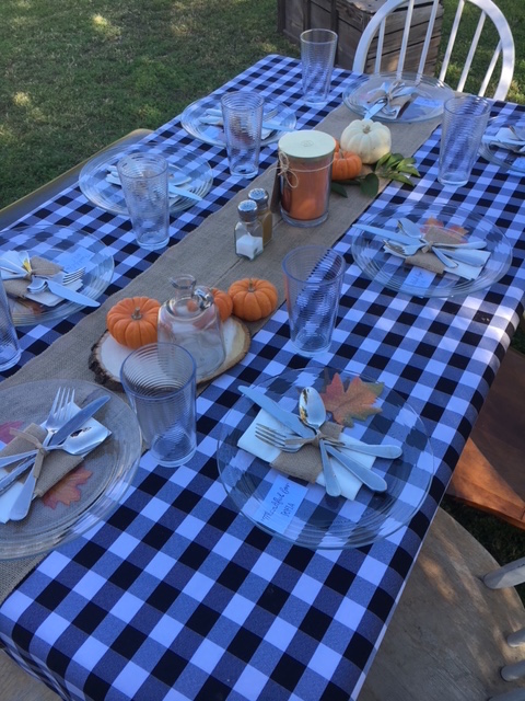The table setting for Friendsgiving is often decked-out with pumpkins, candles and a welcoming tablecloth.