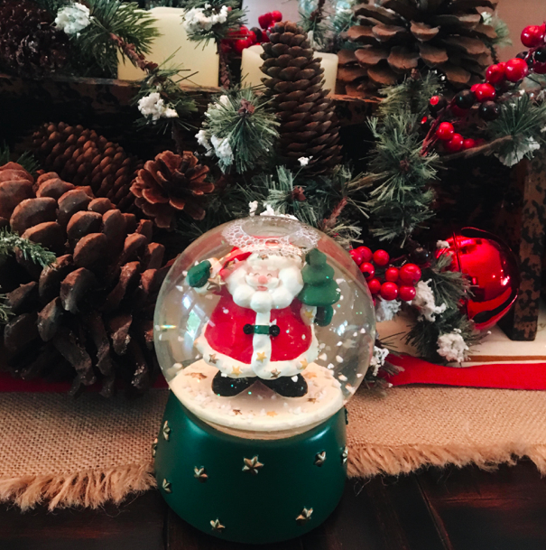A cheerful, Santa snow-globe, festive jingle bells and pine-cones