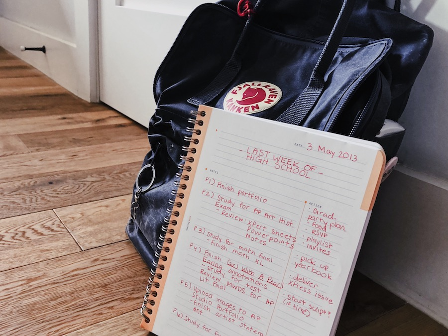 A planner with a list of tasks written down leans against a grey backpack.
