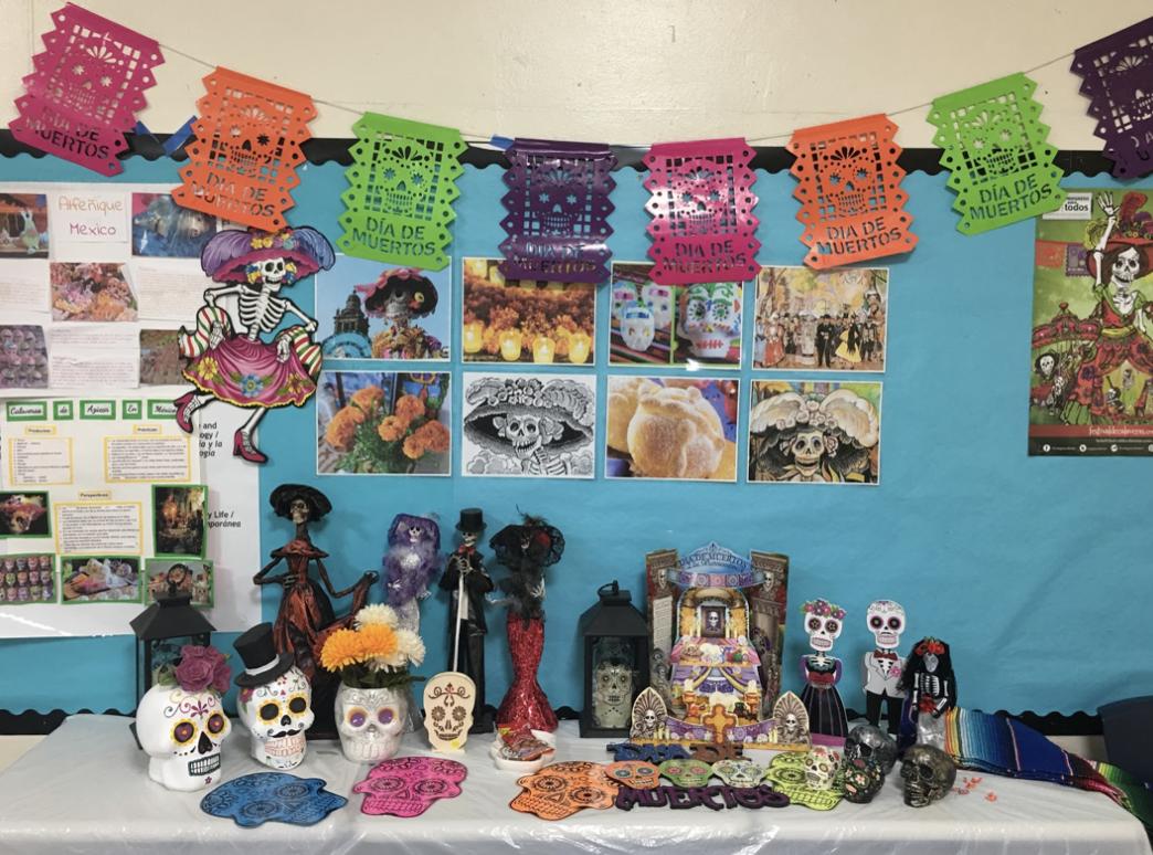 Sra. Gutiérrez's ofrenda is decorated with calaveras, papel picado, photos of other traditional items, and physical depictions of La Calavera Catrina and El Catrín.