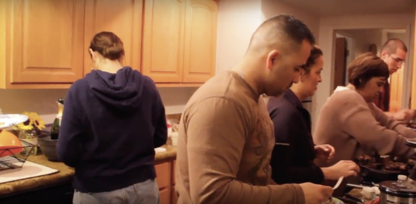 A family spending time together during Thanksgiving. The whole family is in charge of preparing their own dish.
