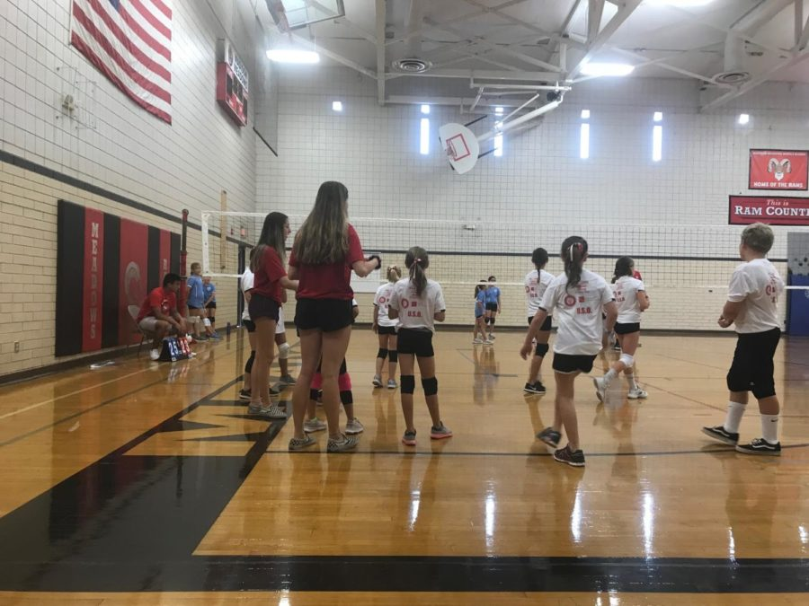 Juniors Alex Lambesis (left) and Hallie Jonkosky (right) are volunteering at the rams gym by aiding the young athletes in a volleyball practice.