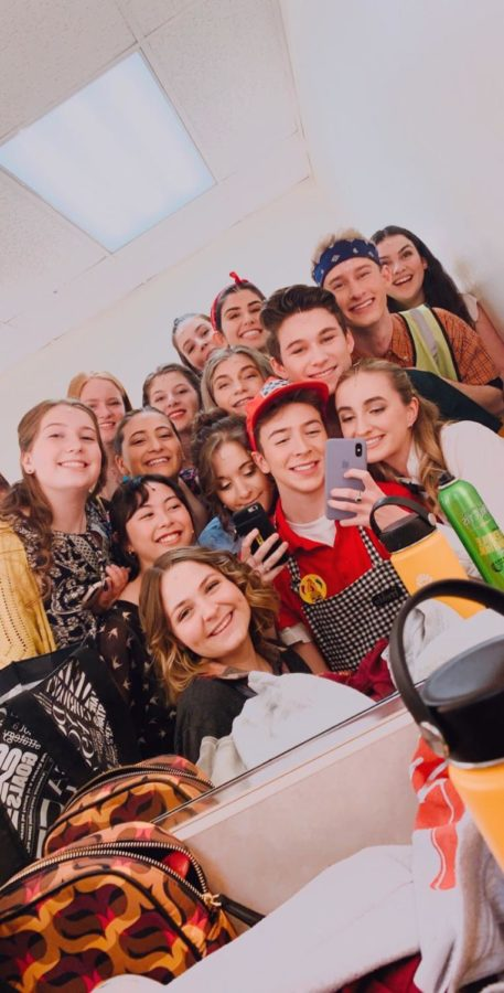 Cast members huddle up to take a mirror selfie backstage before their matinee show.