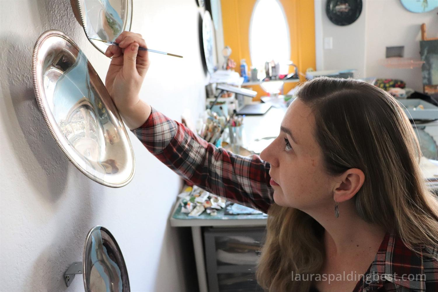 Artist Laura Best works on her creations.