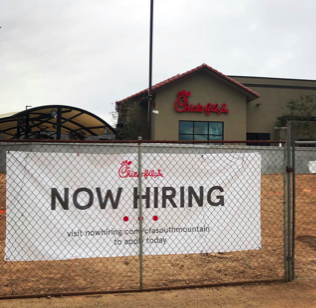 "A ""Now Hiring"" sign in-front of Chik-fil-a, a common workplace for students.  Photo Credit: Janessa Gutierrez"