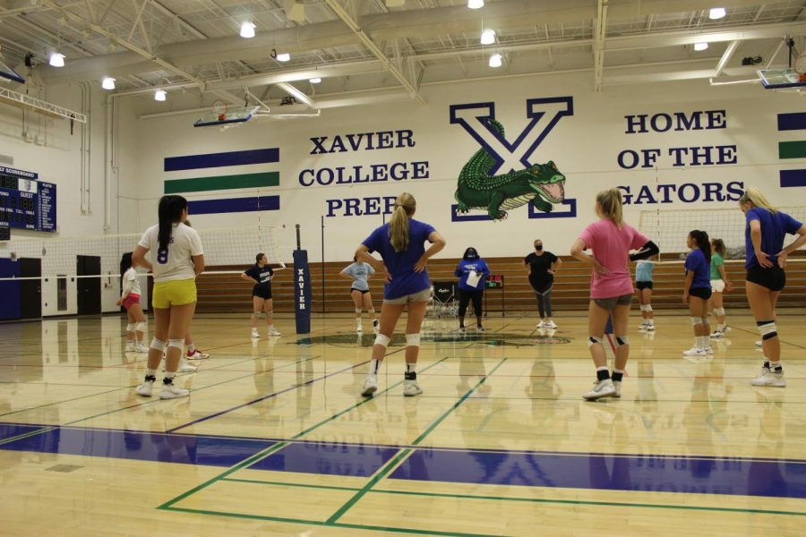 Xavier's varsity volleyball players along with the coaches start off their practice in a socially-distanced group circle.