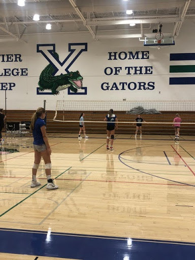 Xavier volleyball players await a serve while practicing hard in the gym for this year's season!