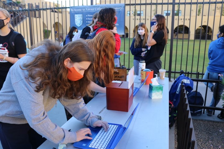 Near Bidwill Circle, a Xavier student logs in her cans on an online Google survey as evidence that she did participate in the food drive. NHS members worked shifts in the morning to monitor the logging-in of cans.