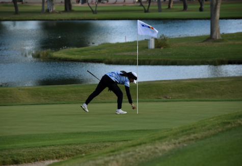 Junior Ivy Song retrieves her ball at the championship on the 18th hole.