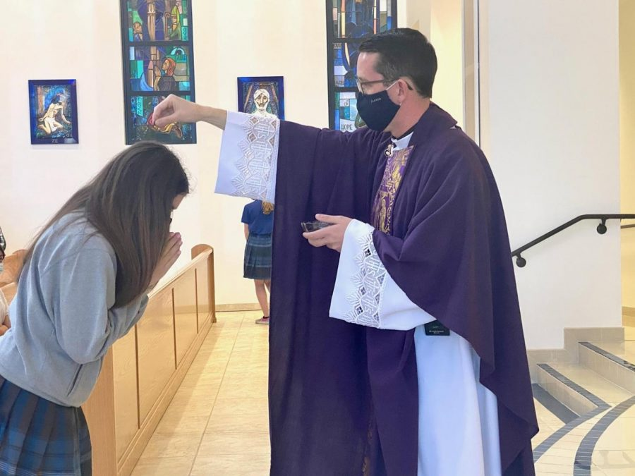 A+Xavier+Eucharistic+minister+receives+ashes+for+this+year%27s+Ash+Wednesday+all-school+Mass+service.