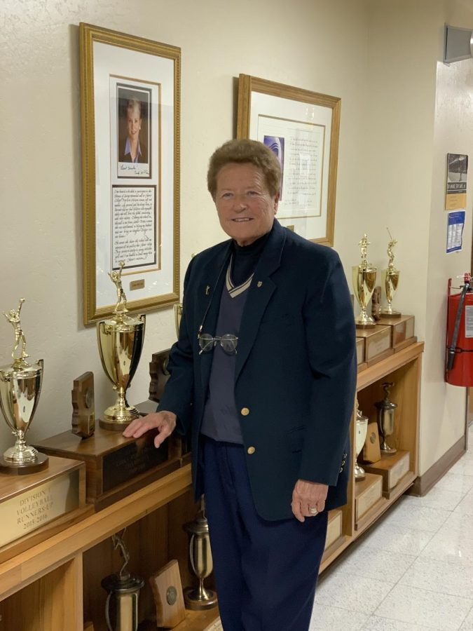 Sister Lynn Winsor, who will soon be inducted into the National Interscholastic Athletic Administration Hall of Fame, poses in a hall of trophies by Xavier's athletic offices.