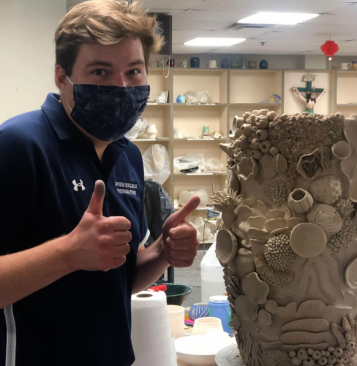 Zachary Carlson, ceramics teacher, stands with a ceramics project. Carlson has been working on providing a creative, yet safe space for students to work.