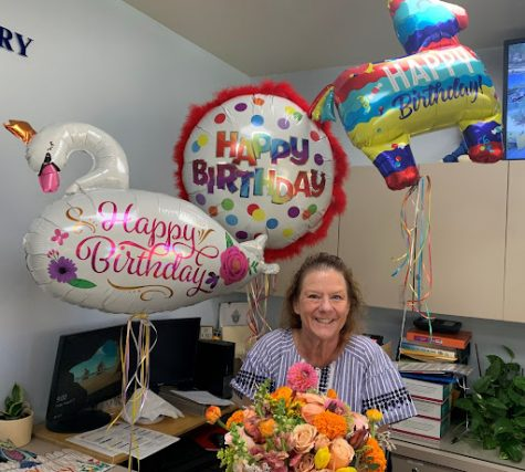 Xavier's Director of Student Attendance, Jerri Butts, receives flowers and balloons from the president of Xavier's Dads' Club, Matt Campisi. Butts was thrilled to be celebrated on her special day.